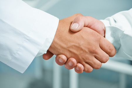 32705291 - man doctor shakes hand with another doctor in hospital, concept of teamwork
